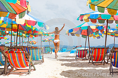 Woman with arms raised running on beach