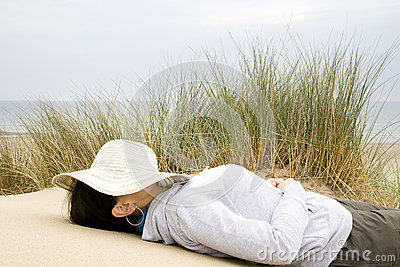 Woman asleep on beach landscape