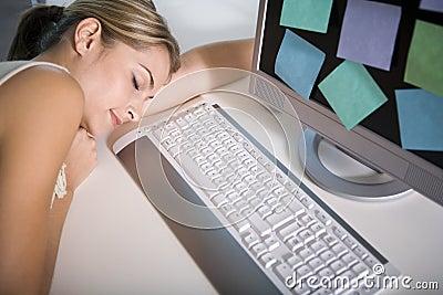 A woman asleep at her computer