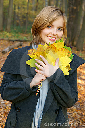 Woman in autumn park with maple leaves