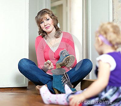 Woman with baby cleans footwear