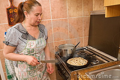 The woman bakes pancakes.