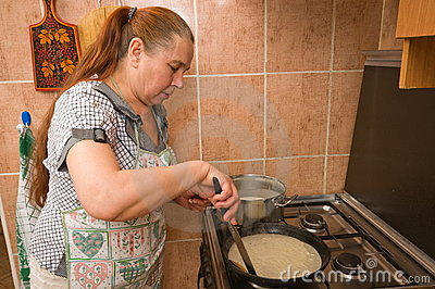 The woman bakes pancakes.