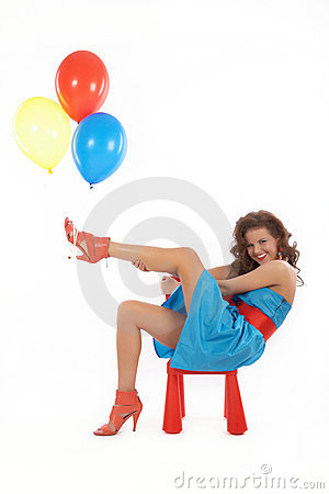 Woman with balloons sitting in a red small chair