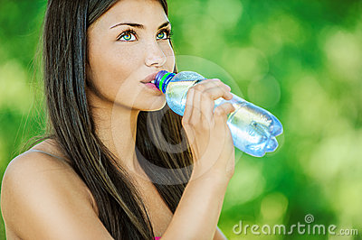 Woman with bare shoulders drinks