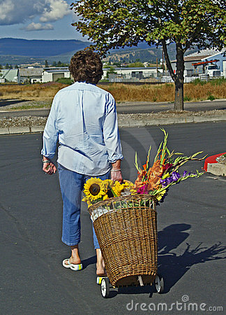 Woman with basket cart with flowers
