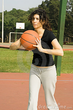 Woman on Basketball Court With Basketball-Vertical