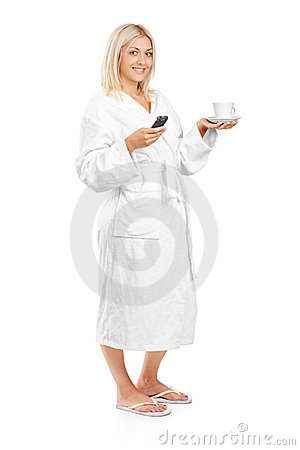 Woman in bathrobe holding a coffee cup and phone