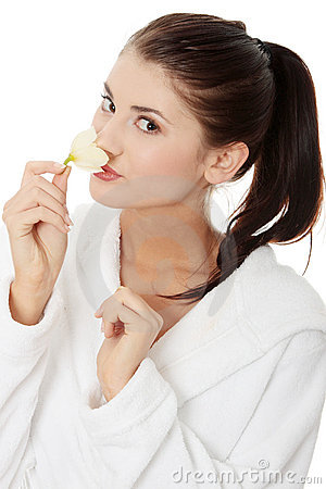 Woman in bathrobe holding orchid flower