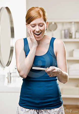 Woman in bathroom viewing positive pregnancy test