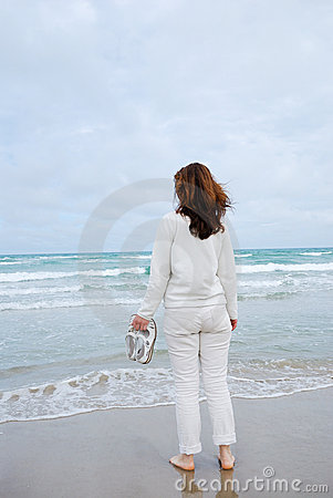 Woman on beach against sea and sky.
