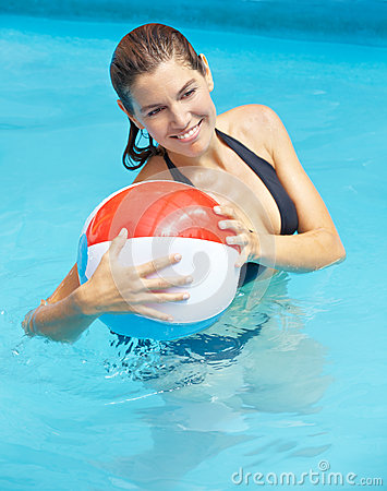 Woman with beach ball in pool