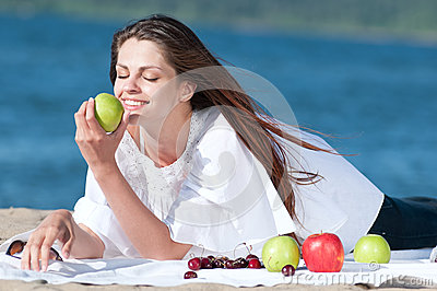 Woman on beach eating fruits
