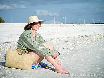 Woman on the beach enjoying the warm weather