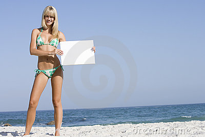 Woman on beach holding blank card