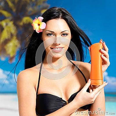 Woman on the beach  holds orange sun tan lotion bottle.