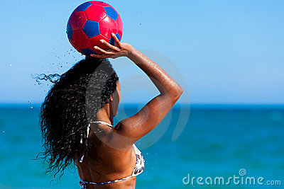 Woman at the beach playing soccer