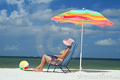 Woman on the beach sittin on a chair