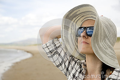 Woman on beach with sun hat