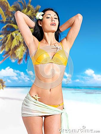 Woman with beautiful body in bikini at beach