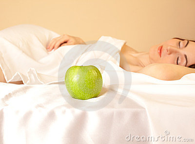 Woman in bed with apple (focus on apple)