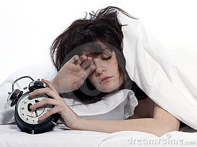 Woman in bed awakening tired holding alarm clock