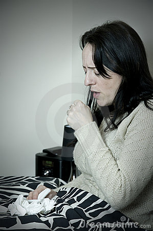 Woman in bed coughing, sneezing into hand