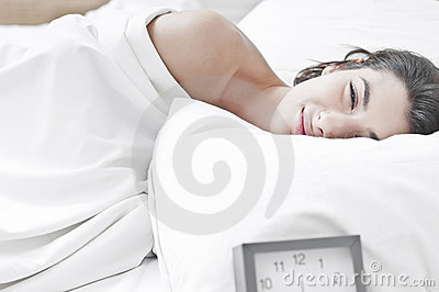 Woman on bed in the morning with a clock ringing