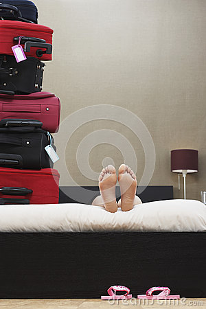 Woman In Bed Next To Stack Of Suitcases Stock Photo