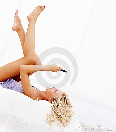 Woman on the bed using cellphone to text message
