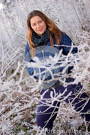 Woman behind frosty twigs