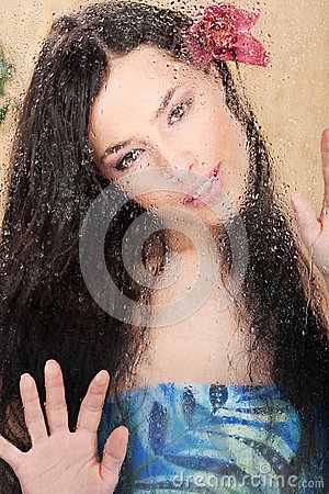 Woman behind glass full of water drops