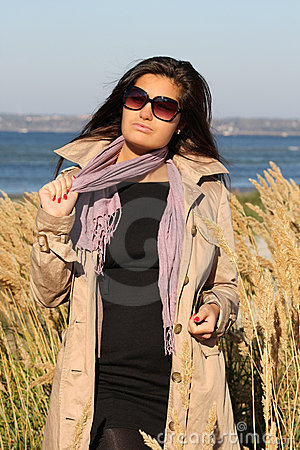 Woman in beige autumn coat posing at beach