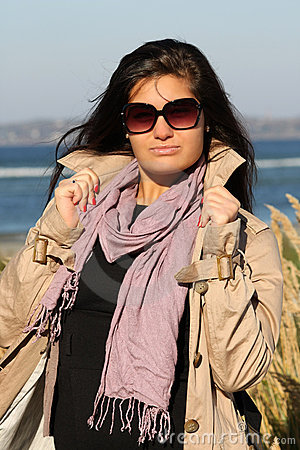 Woman in beige autumn coat standing at beach