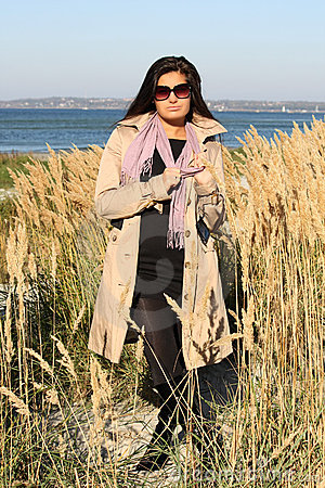 Woman in beige autumn coat standing by the sea