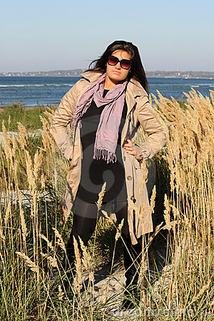 Woman in beige autumn coat standing at seaside