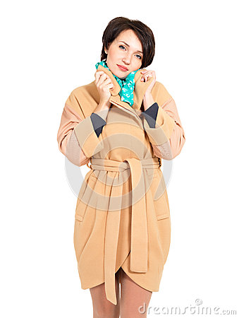 Woman in beige fall coat with green scarf