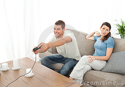 Woman being bored while her boyfriend playing