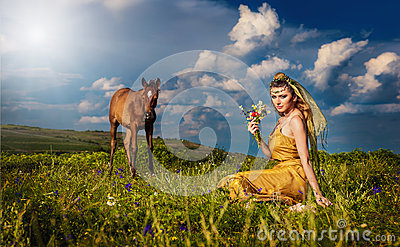 Woman belly dancer relaxing on grass field against blue sky with white clouds
