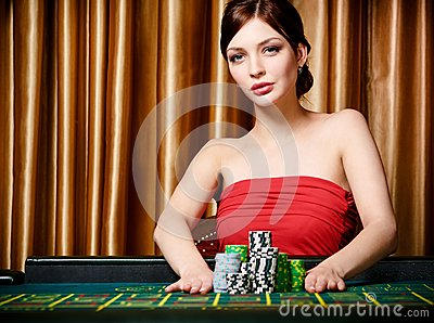 Woman bets pile of chips playing roulette