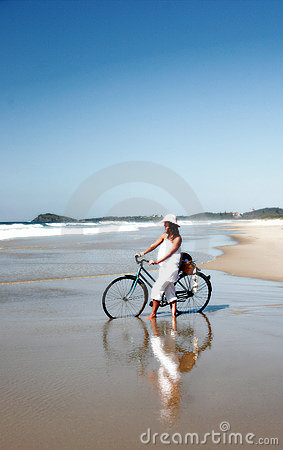 Woman with bicycle on beach