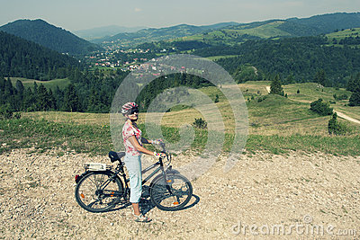 Woman on a bicycle in mountains
