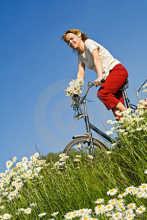 Woman with bicycle among spring flowers