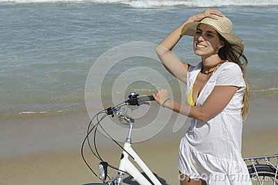 Woman with bike on the beach