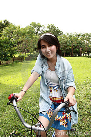 Woman with a bike outdoors smiling