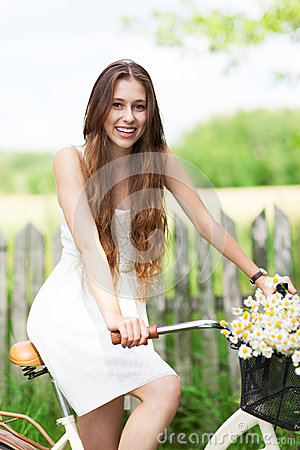 Woman with bike by wooden fence