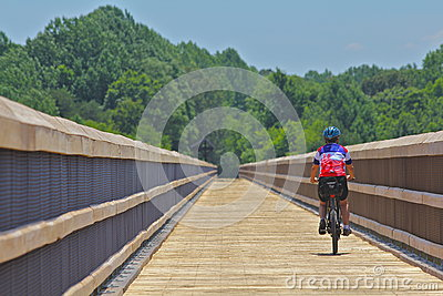 Woman biking a bridge on a Virginia Trail