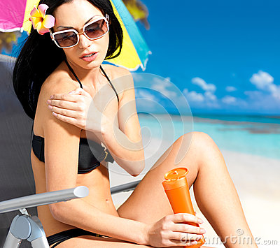 Woman in bikini applying sun block cream on body