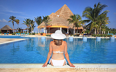 Woman in a bikini by beach resort swimming pool