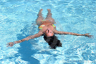 Woman in bikini floating in swimming pool